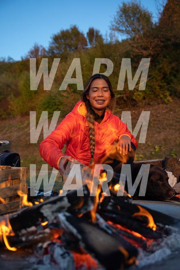 Vrouw bij het kampvuur met winterjasje